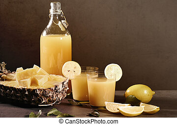 Bottle of homemade pineapple juice with ginger, lemon and ingredients.