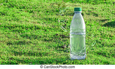 Bottle of mineral water with splash effect in the middle of a green grass background