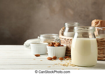 Bottle of oat milk, basket with a glasses of different types milk on wooden background, space for text