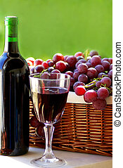 bottle of red wine, a glass of wine and  grapes
