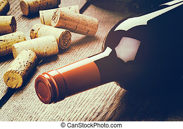 Bottle of red wine and corks on wooden table