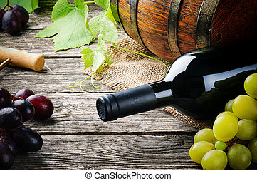 Bottle of red wine and fresh grape on wooden table