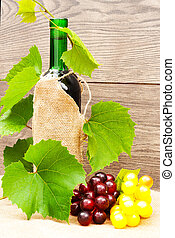 bottle of red wine and vine on a wooden background