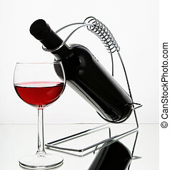 Bottle of red wine on holder with glass on white background