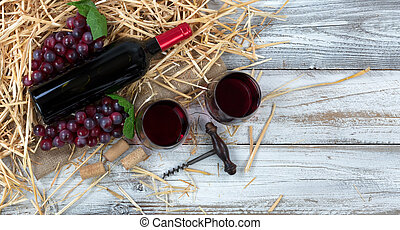 Bottle of red wine plus drinking glasses on top of straw and burlap with white rustic wooden boards underneath