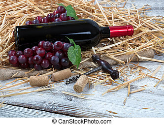 Bottle of red wine plus grapes on top of straw and burlap with white rustic wooden boards underneath