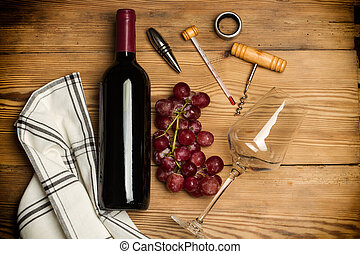 Bottle of red wine, red grapes and wine accesories