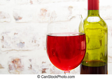 Bottle of red wine with glass ready to pour