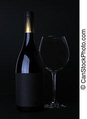 Bottle of red wine with glass with black background