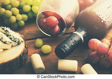 bottle of red wine with grapes and blue cheese