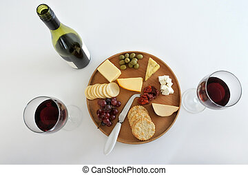 Bottle of red wine with two wineglasses served  with cheese platter