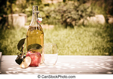 Bottle of refreshing apple juice squeezed from fresh apples harvested in the garden standing outdoors on a rustic wooden table