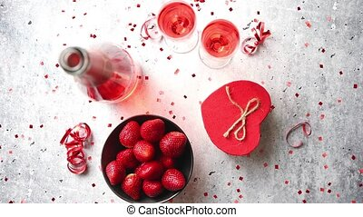 Bottle of rose champagne, glasses with fresh strawberries...