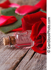 Bottle of rose water and red roses vertical close up -...