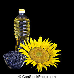 Bottle of sunflower oil with flower and seed isolated on black background