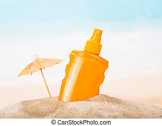 Bottle of sunscreen in the sand against sea.