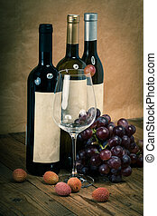 bottle of vine with wine glass and grapes, on wooden background