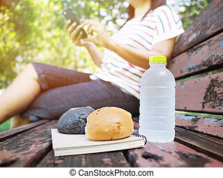 bottle of water and homemade breads on vintage bench in the park.