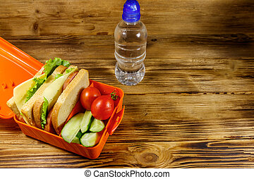 Bottle of water and lunch box with sandwiches and fresh vegetables on a wooden table