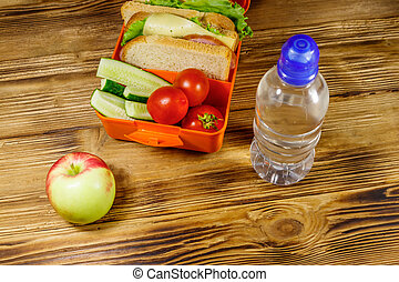 Bottle of water, apple and lunch box with sandwiches and fresh vegetables on a wooden table