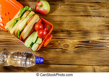 Bottle of water, apple and lunch box with sandwiches and fresh vegetables on a wooden table. Top view, copy space