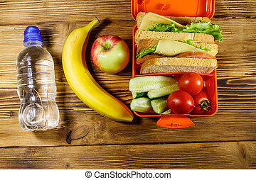 Bottle of water, apple, banana and lunch box with sandwiches and fresh vegetables on a wooden table. Top view