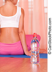 Bottle of water in front of sporty woman