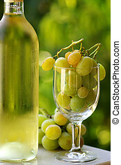 Bottle of white wine with full glass of grapes.