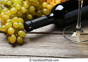 Bottle of white wine with grapes on grey wooden background