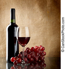 Bottle of wine and a bunch of red grapes - A bottle and a ...