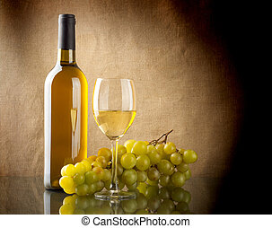 Bottle of wine and a bunch of white grapes - A bottle and a ...