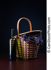 bottle of wine and basket with grapes