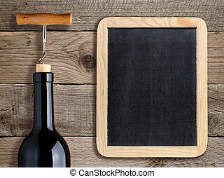 Bottle of wine and blank blackboard on wooden background
