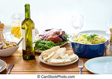 bottle of wine and food on served wooden table