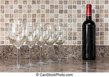 Bottle of wine and glasses on kitchen countertop - Bottle of...