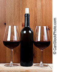 bottle of wine and two wineglasses with red wine