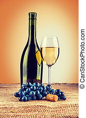 bottle of wine and wineglass with branch of grape on burlap inst