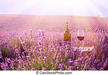 Bottle of wine against lavender landscape.