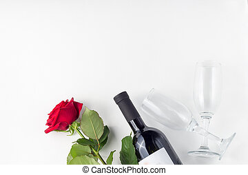 Bottle of wine, glass and red rose with petals on a white background