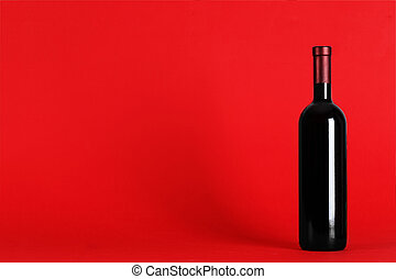 bottle of wine on a red background with space for text. top view