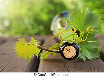 Bottle of wine on the wooden table outdoors