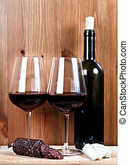 bottle of wine, two wineglasses, cheese and sausage