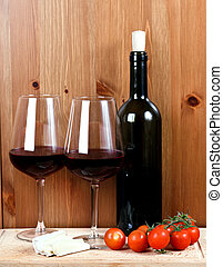 bottle of wine, two wineglasses, cheese and tomatoes