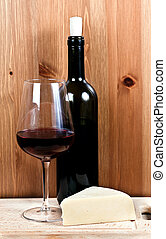 bottle of wine, wine glass with red wine and cheese