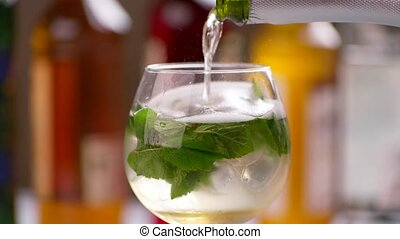 Bottle pours drink into wineglass. Mint leaves in bubbly...