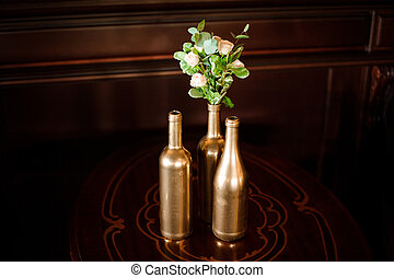 Bottle-shaped vases in golden tone with little bouquet of flowers
