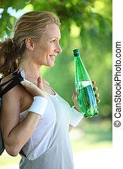bottle., sorrindo, sportswoman, segurando
