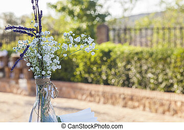 Bottle with bouquet over garden background