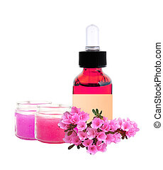 bottle with essence oil and pink flowers isolated on white