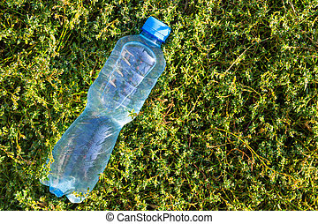 Bottle with fresh clean water on green grass